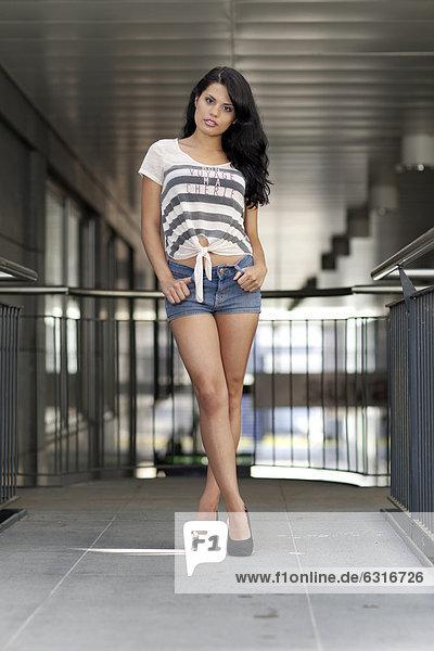 Junge Frau mit gestreiftem T-Shirt  Jeans-Hotpants und hochhackigen schwarzen Schuhen posiert an Geländer