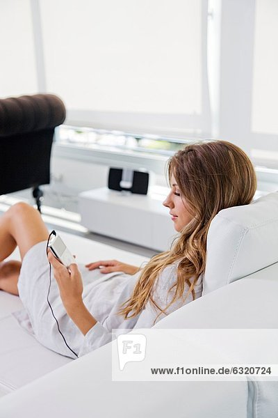 Pretty blonde woman listening to music on the sofa