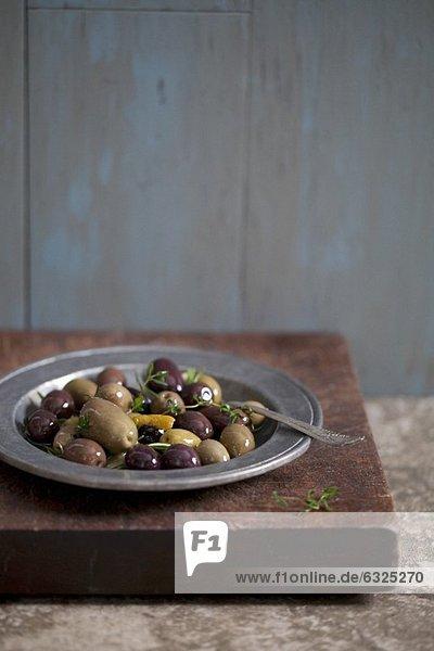 Verschiedene eingelegte Oliven mit Thymian auf Teller