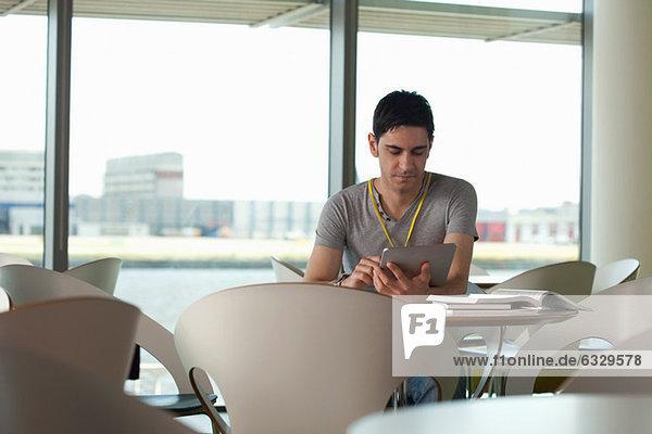 Mann mit digitalem Tablett im Café
