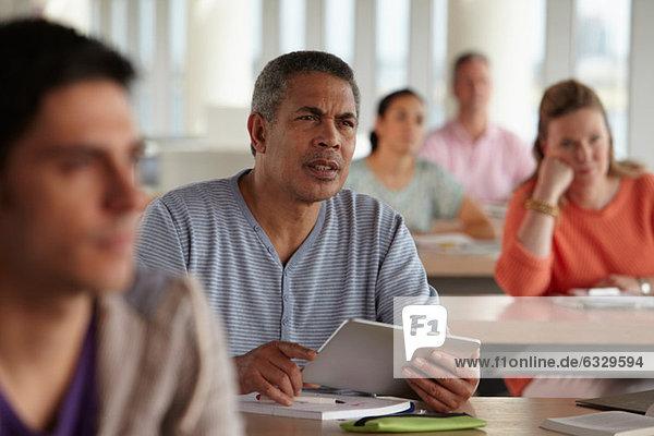 Mann mit digitalem Tablett im Unterricht