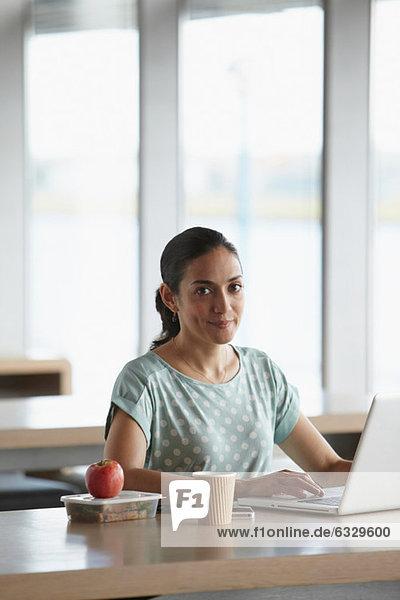 Frau mit Laptop mit Lunchpaket auf dem Schreibtisch