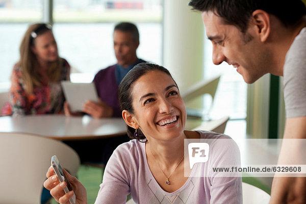 Frau zeigt Mann Smartphone