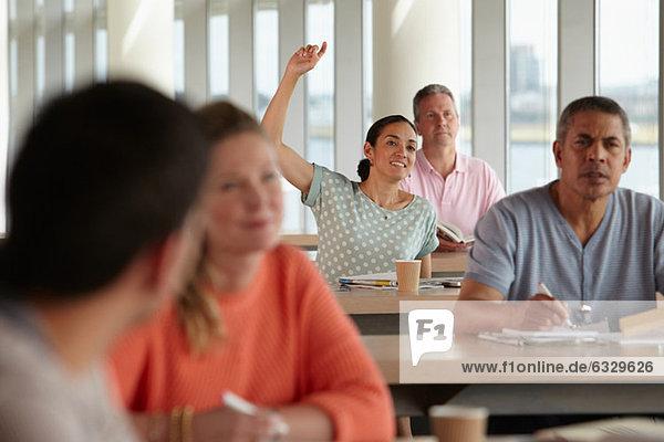 Reife Schüler im Unterricht  Frau mit erhobener Hand