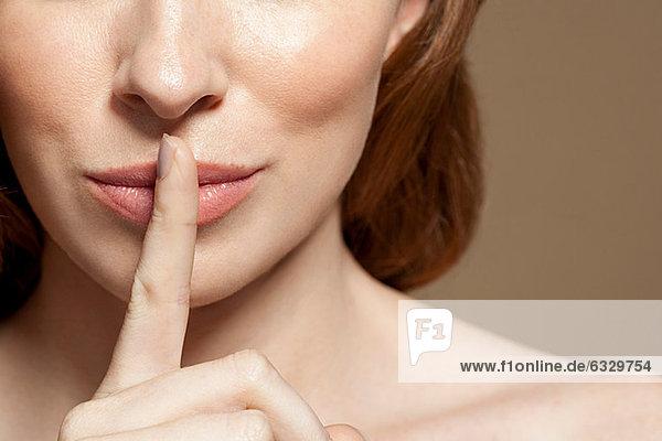 Frau mit Finger auf den Lippen  Nahaufnahme  Mund