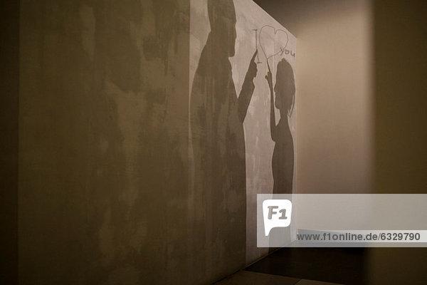 Schatten des Paares und Botschaft der Liebe an der Wand