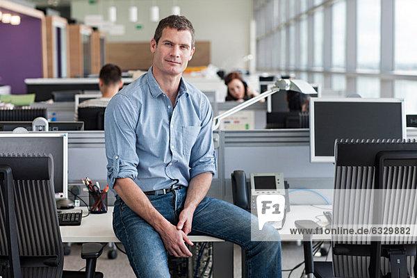 Porträt eines auf dem Schreibtisch sitzenden Mannes