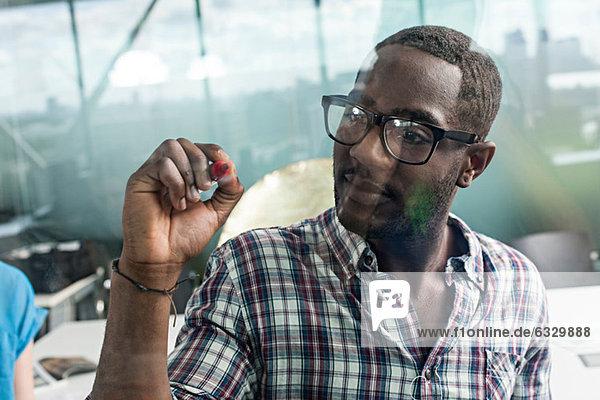 Mann schreibt auf Glas