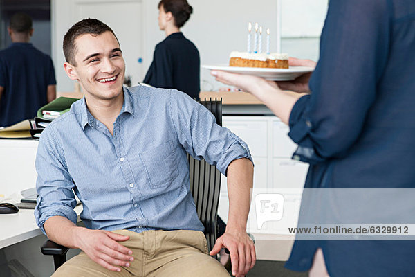 Woman bringing male colleague birthday cake in office