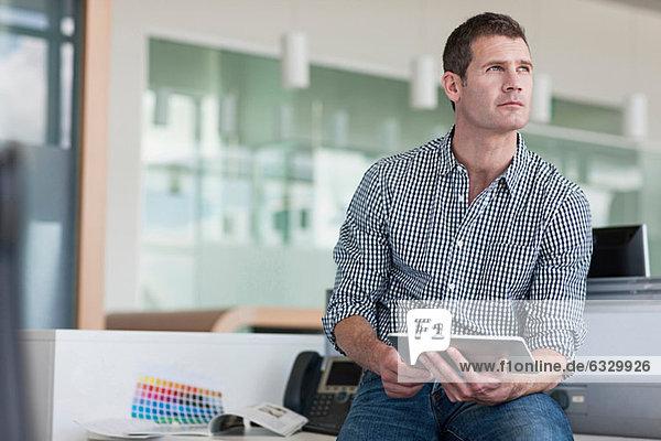 Mann mit digitalem Tablett schaut weg