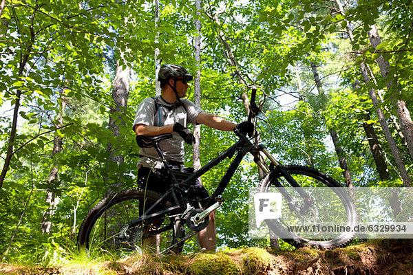 Mann im Wald mit Mountainbike