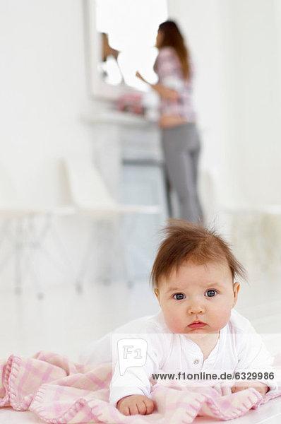Mädchen mit Mutter im Hintergrund