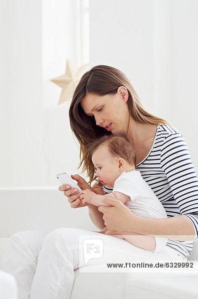 Mutter hält Baby und benutzt Handy