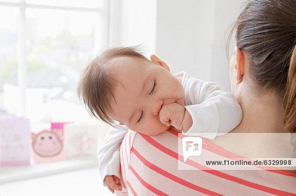 Baby Mädchen schläft auf der Schulter der Mutter