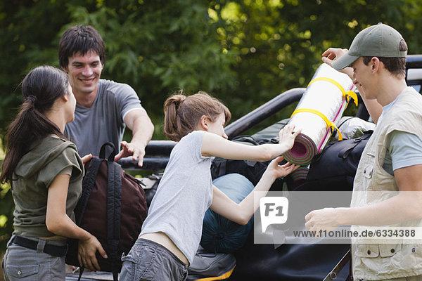 Junge Männer helfen jungen Frauen beim Verladen der Campingausrüstung auf die Ladefläche des Pick-up Trucks