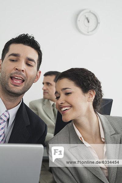 Kollegen  die am Laptop arbeiten