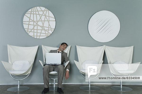 Jungunternehmer schläft im Sessel mit Laptop auf dem Schoß