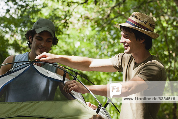 Young men setting up tent in woods