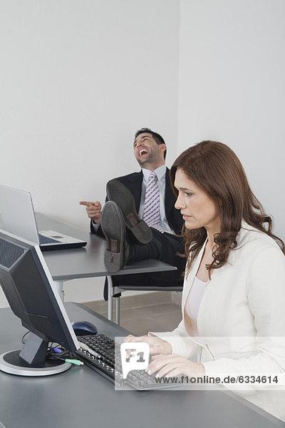 Geschäftsfrau im Büro  Kollegin lacht im Hintergrund