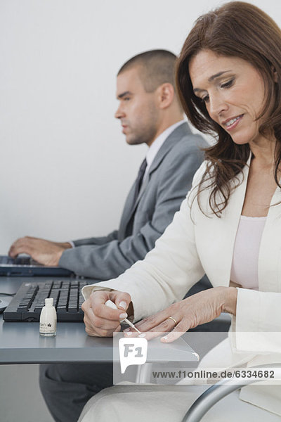 Reife Geschäftsfrau beim Auftragen von Nagellack im Büro