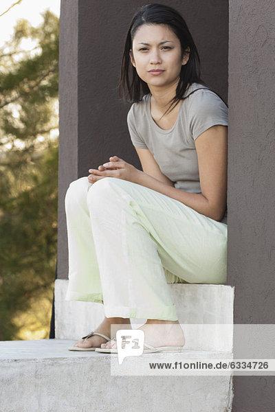 Junge Frau im Freien sitzend  in Gedanken wegschauend