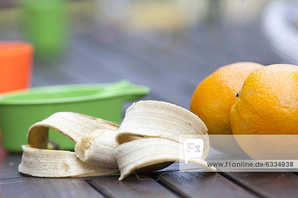 Orangen und halb gegessene Banane
