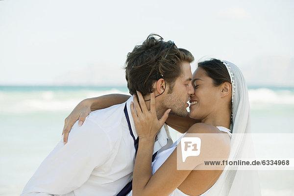 Brautpaar beim Küssen am Strand