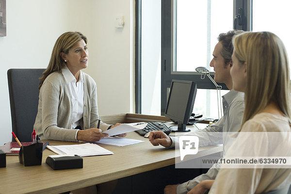 Geschäftsfrau im Gespräch mit Kunden im Büro