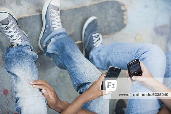 Junge Männer  die Mobiltelefone benutzen  abgeschnitten. Junge Männer, die Mobiltelefone benutzen, abgeschnitten.