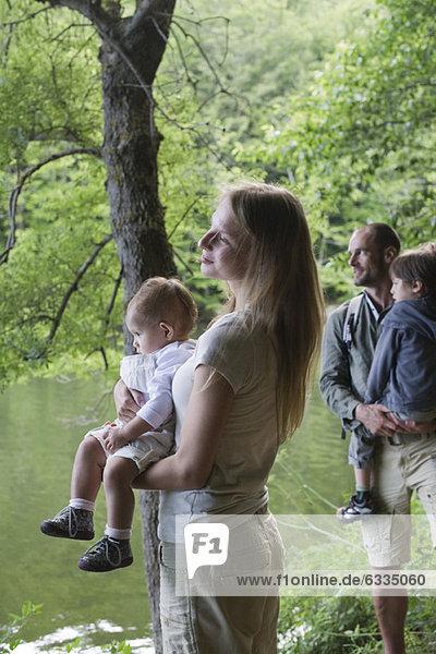 Familie im Wald mit Blick auf den Fluss  Konzentration auf die Mutter mit dem kleinen Mädchen