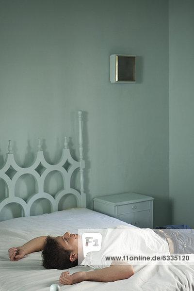 Mann entspannt auf dem Bett  schaut verträumt nach oben