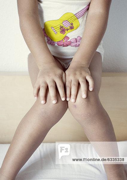 Mädchen auf Kopfteil sitzend  Mittelteil