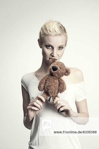 Junge Frau beißt Teddybär  Portrait