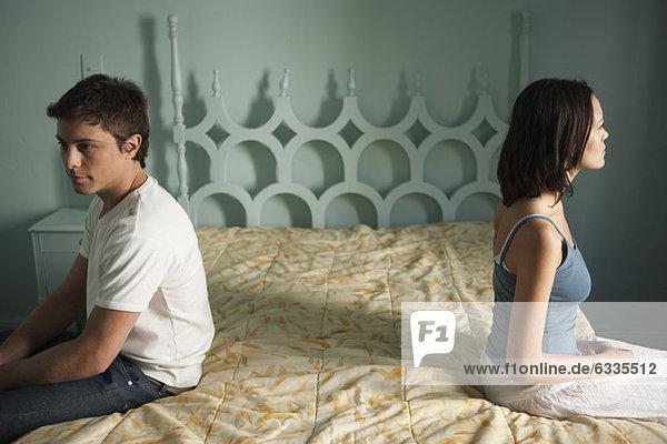 Paar auf getrennten Seiten des Bettes sitzend  beide mit Blick in die Ferne