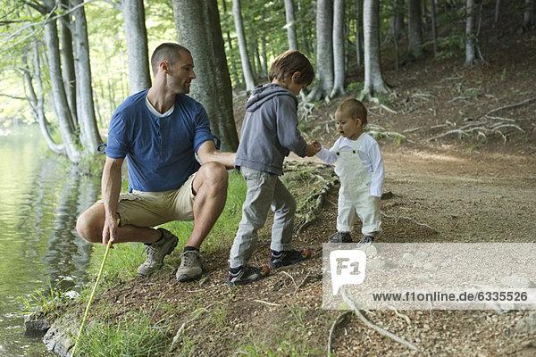 Junge zeigt kleine Schwester Fische  die er gerade gefangen hat.