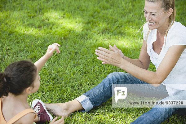 Mutter und Tochter spielen auf Gras Mutter und Tochter spielen auf Gras