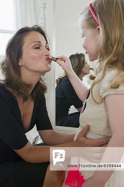 Mädchen legt Lippenstift auf Mutter