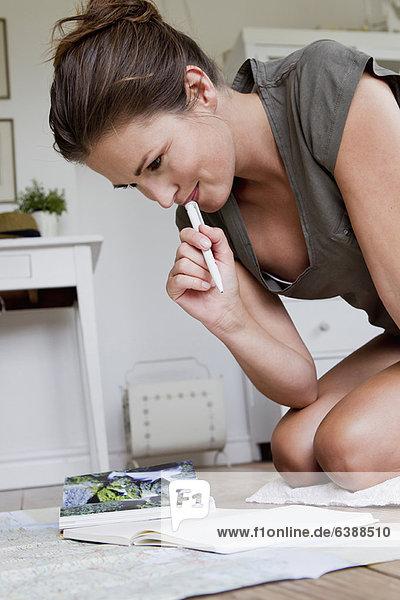 Frau liest Karten auf dem Boden