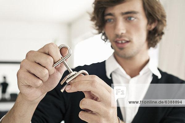 Teenager-Junge bei der Arbeit am Metallpuzzle
