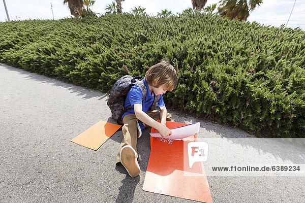 Junge zieht Hausaufgaben aus dem Ordner