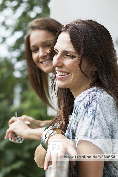 Lächelnde Frau stützt sich auf das Geländer