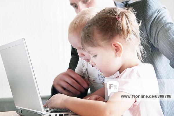Vater und Kinder spielen mit dem Laptop