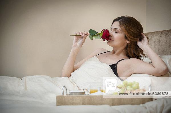 Frau entspannt mit Frühstück im Bett