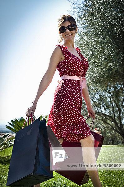 Frau trägt Einkaufstaschen im Gras