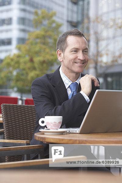 Geschäftsmann bei der Arbeit am Laptop im Café