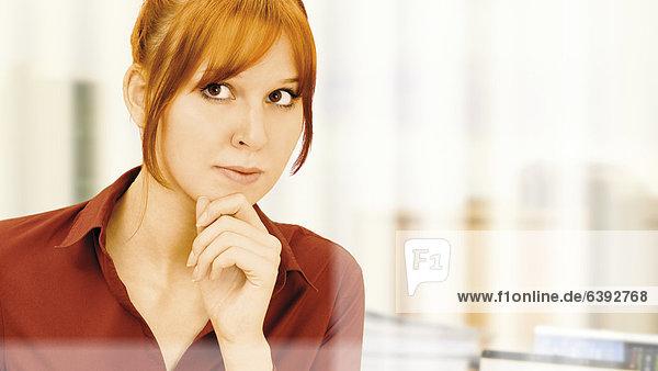 Konzentrierte  nachdenkliche junge Geschäftsfrau im Büro