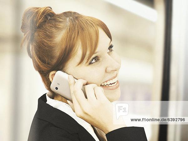 Portrait einer jungen sympathischen Geschäftsfrau mit Handy