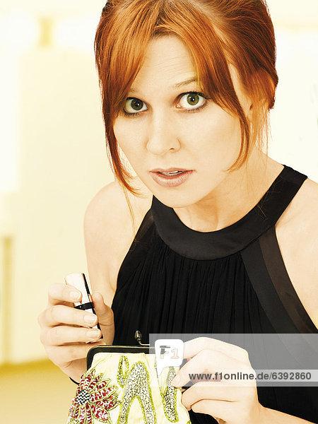 Überraschte elegante junge Frau in Abendgarderobe holt Lippenstift aus Abendtäschchen