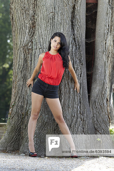 Junge Frau mit rotem Top  schwarzen Hotpants und hochhackigen Schuhen posiert stehend vor Baum