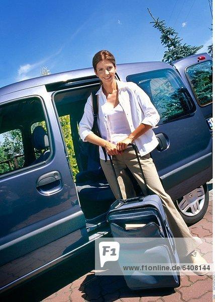 Frau packt ihren Koffer ins Auto